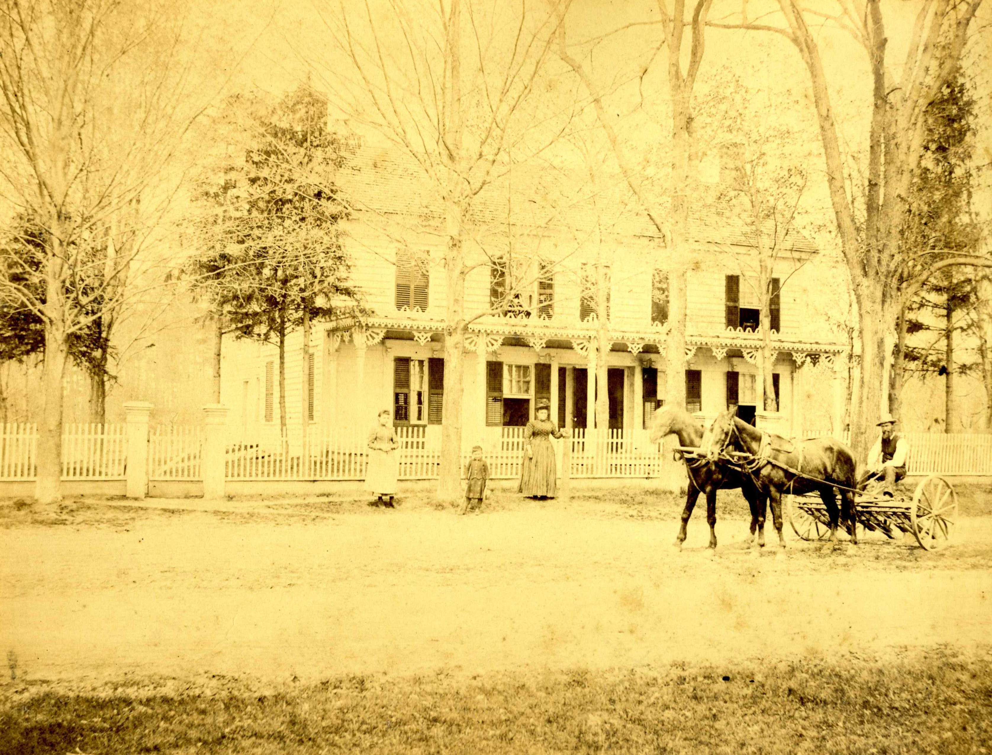 The New Concord b&b in a photo from the 1800's with two horses and a buggy